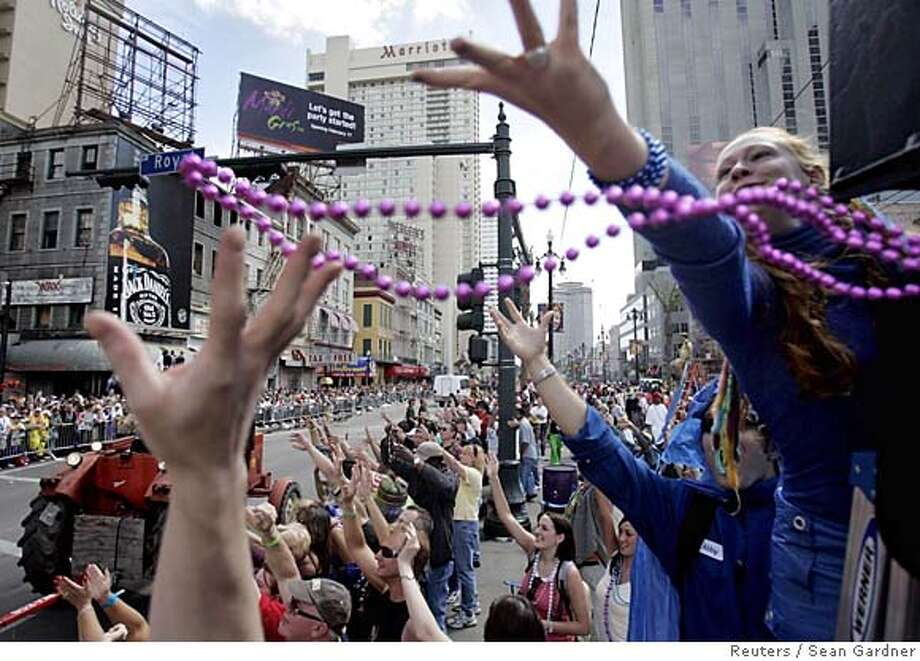 Revellers reach out for beads on Canal Street as the Krewe of Zulu rolls by while celebrating Mardi Gras in New Orleans February 28, 2006. Thousands celebrated the last day of the carnival season on Tuesday. REUTERS/Sean Gardner 0 Photo: SEAN GARDNER