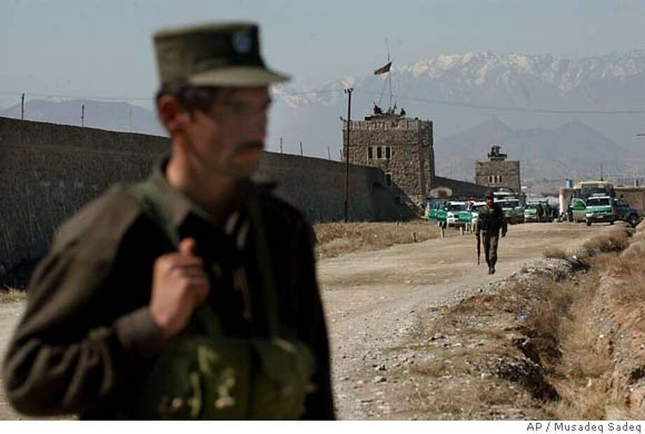 An Afghan police officer stands, as the Policharki Prison is seen at the background in Kabul, Afghanistan on Sunday, Feb. 26, 2006. Hundreds inmates, including terrorism convicts, clashed with guards in a failed attempt to break out of a high-security prison in Kabul, then took control of parts of the prison, officials said Sunday. (AP / Musadeq Sadeq)