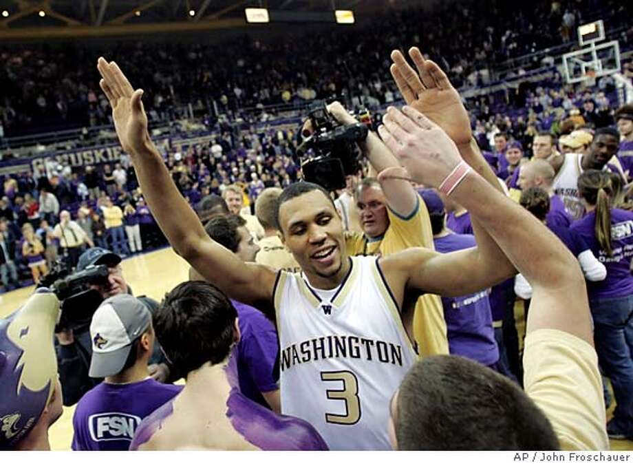 Washington's Brandon Roy receives high fives from fans after the 73-62 win over California in a PAC-10 basketball game in Seattle Sunday, Feb. 26, 2006. Roy led the scoring with 27 points and played his final home game along with four other seniors. (AP Photo/John Froschauer) Photo: JOHN FROSCHAUER