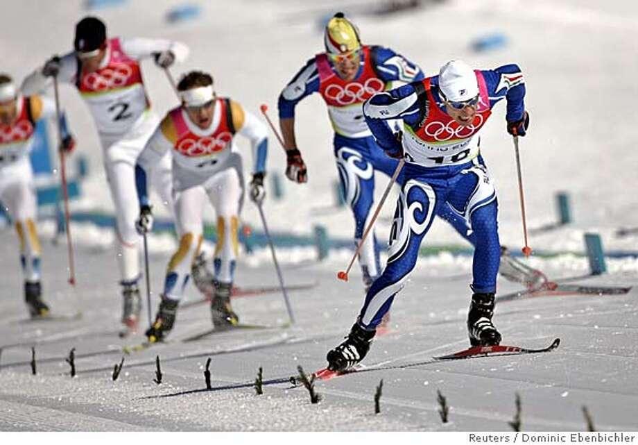 Italy's Giorgio di Centa (R) skis to win the men's 50km cross country race at the Torino 2006 Winter Olympic Games in Pragelato, Italy, February 26, 2006. Di Centa won the race ahead of Russia's Eugeni Dementiev and Austria's Mikhail Botwinov. REUTERS/Dominic Ebenbichler Photo: DOMINIC EBENBICHLER