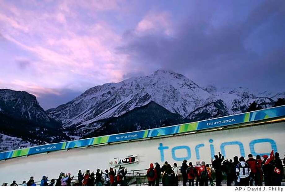 Canada's CAN-2 bobsled piloted by Serge Despres turns through curve 14 as the sun sets behind the mountains during the first run of the Olympic Men's Two-Man Bobsled competition at the Turin 2006 Winter Olympic Games in Cesana Pariol, Italy, Saturday, Feb. 18, 2006. (AP Photo/David J. Phillip) Photo: DAVID J. PHILLIP