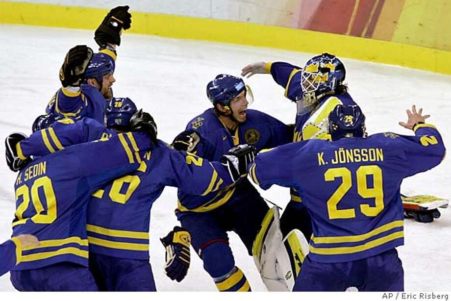 Team Sweden celebrates defeating Finland 3-2 in the gold medal ice hockey match at the 2006 Turin Winter Olympic Games in Turin, Italy Sunday Feb. 26, 2006. Sweden's goaltender Henrik Lundqvist is behind Kenny Jonsson (29). (AP Photo/Eric Risberg) Photo: ERIC RISBERG