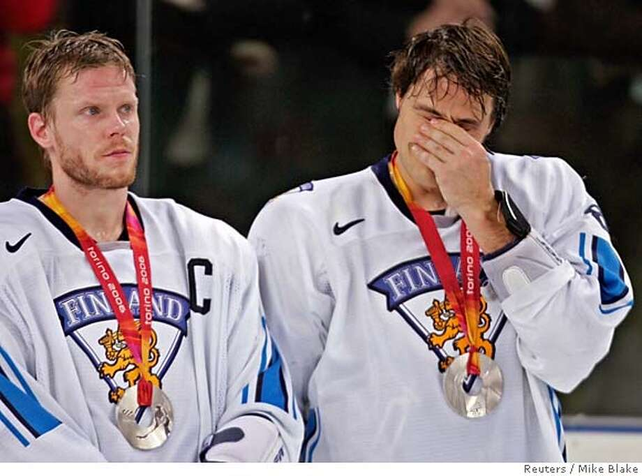 Finnish forward Teemu Selanne (R) and captain Saku Koivu react after the men's gold medal ice hockey game against Sweden at the Torino 2006 Winter Olympic Games in Turin, Italy February 26, 2006. Sweden won the match 3-2. REUTERS/Mike Blake Photo: MIKE BLAKE