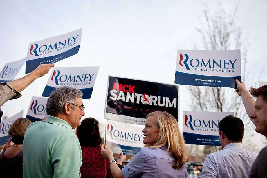 Rock Erekson (L), a Mitt Romney supporter, and Libby Wilkinson (C), a Rick Santorum supporter, display signs before Republican presidential candidate, former U.S. Sen. Rick Santorum was to arrive for a campaign stop March 17, 2012 at Westminster Christian Academy, a caucus location in Town and Country, Missouri. Rick Santorum will compete in Missouri's caucus today after winning a non-binding primary held in the state on February 7. Photo: Whitney Curtis, Getty Images