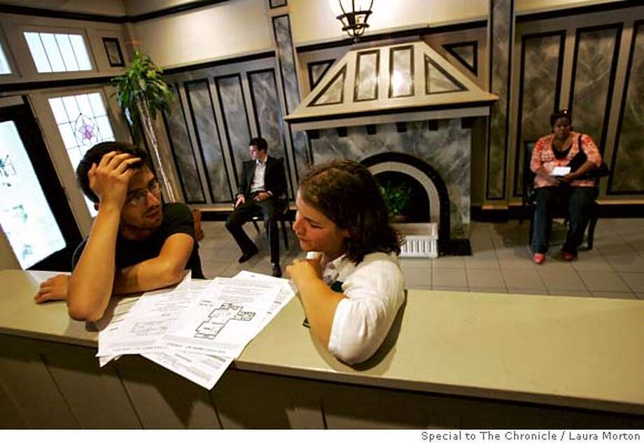 .jpg Denis Trotabas and Carolina Raga, who both recently moved to San Francisco from France, look over floor plans while waiting with several others to view an apartment for rent in Nob Hill during an open house. The San Francisco rental market has tightened up recently, making apartments harder to find. (Laura Morton/Special to the Chronicle) *** Denis Trotabas  *** Caroline Raga Photo: Laura Morton