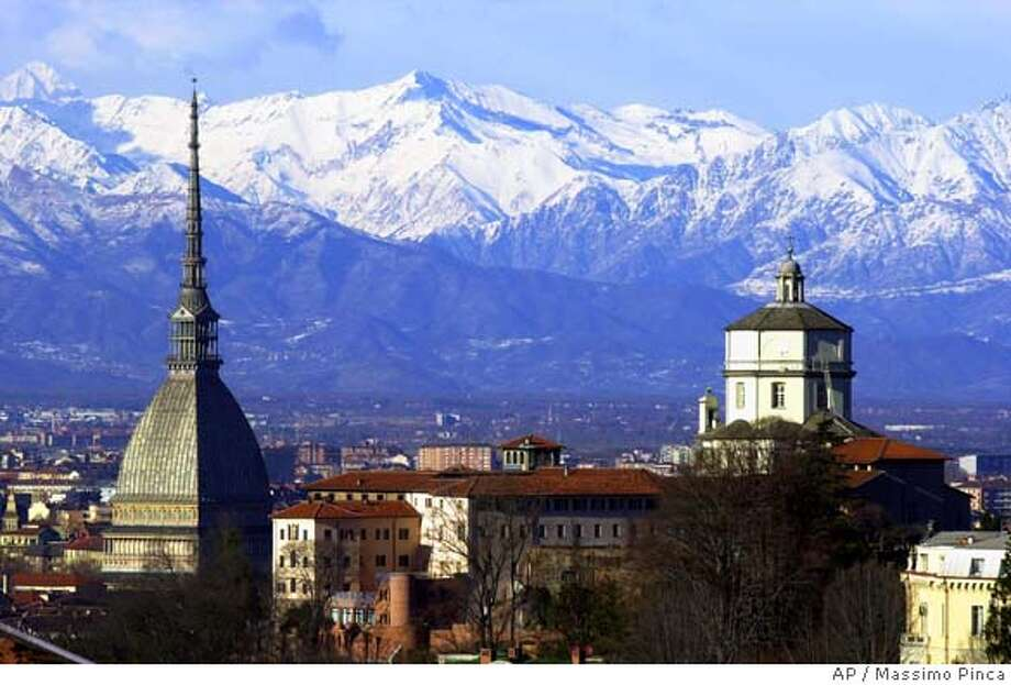 The Mole Antoneliana, left, The Italian city of Turin's most famous landmark is backdropped by the mountains, in Turin Monday Feb. 20, 2006. The Turin 2006 Winter Olympic Games are continuing in this historic northwestern Italian city. History has not always been kind to this rich outpost in northwest Italy. Hannibal came through and burned it to the ground. The French showed up several times, once led by Napoleon, and took the region for its own. Now it's held captive by all things Olympic. Streets are closed. Detours abound. Businesses near the skating oval are hurting. But the end is near. Though the Piedmont province is no stranger to be invaded, it also is no stranger to watching its captors come and go.(AP Photo/Massimo Pinca) Photo: MASSIMO PINCA