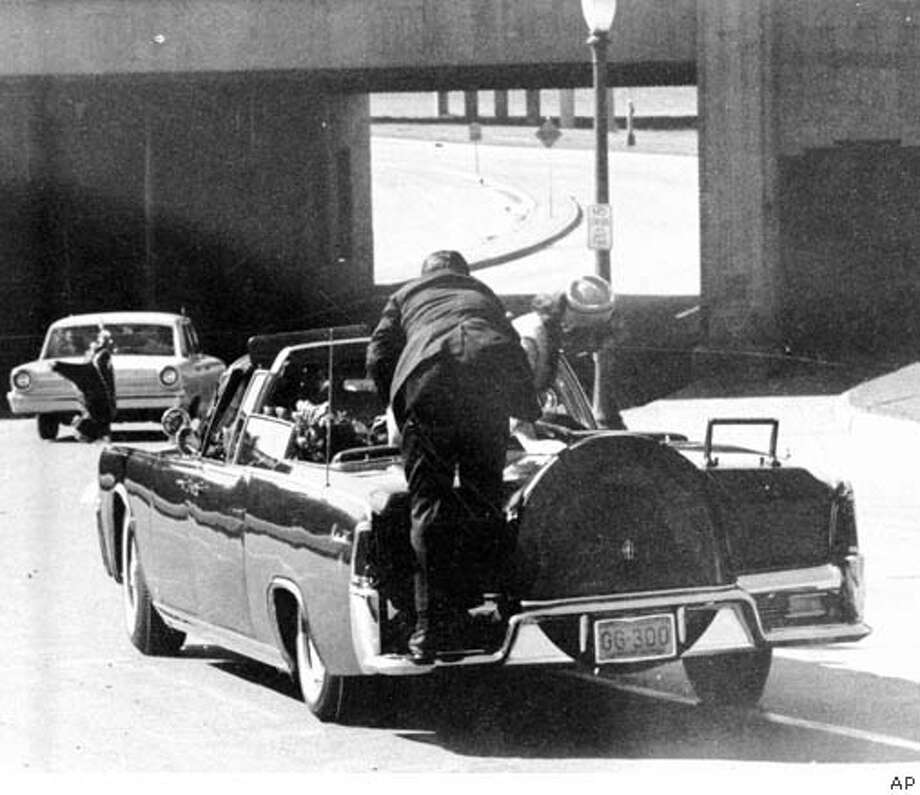 President John F. Kennedy is slumped in the backseat of this car immediately after being shot in Dallas, Texas, Nov. 22, 1963. Jacqueline Kennedy leans over the president at right as a Secret Service agent stands on the bumper. Associated Press File Photo, 1963