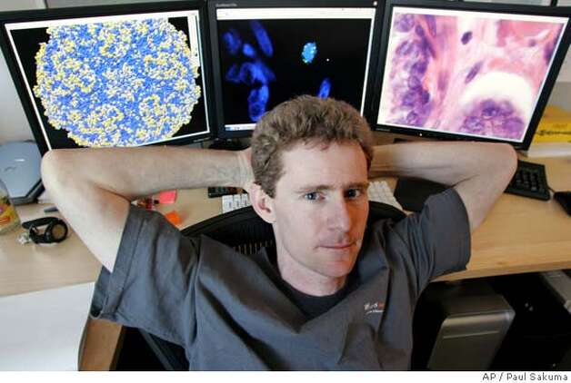 University of California, San Francisco researcher Joe DeRisi poses with photos on his computer of a virus structure, left, prostate tissue, center, and another virus, right, in his office in San Francisco, Wednesday, Feb. 22, 2006. On Friday, Feb. 24, 2006, researchers at the UCSF and the Cleveland Clinic plan to announce they had found a virus never before seen in humans in cancerous prostates removed from men with a certain genetic defect. (AP Photo/Paul Sakuma) Photo: PAUL SAKUMA