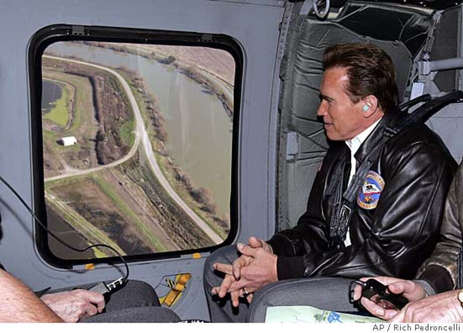 California Gov. Arnold Schwarzenegger views a portion of the levee along the Sacramento River while getting a tour of the levees in a California National Guard Helicopter, near Sacramento, Calif., Wednesday, Feb. 22, 2006. Schwarzenegger, who has announced that he wants to spend $2.5 billion over the next 10 years to strengthen levees and improve the flood managment system, called on the federal government to provide federal funds to help cover the costs. (AP Photo/Rich Pedroncelli, Pool) POOL PHOTO Photo: RICH PEDRONCELLI