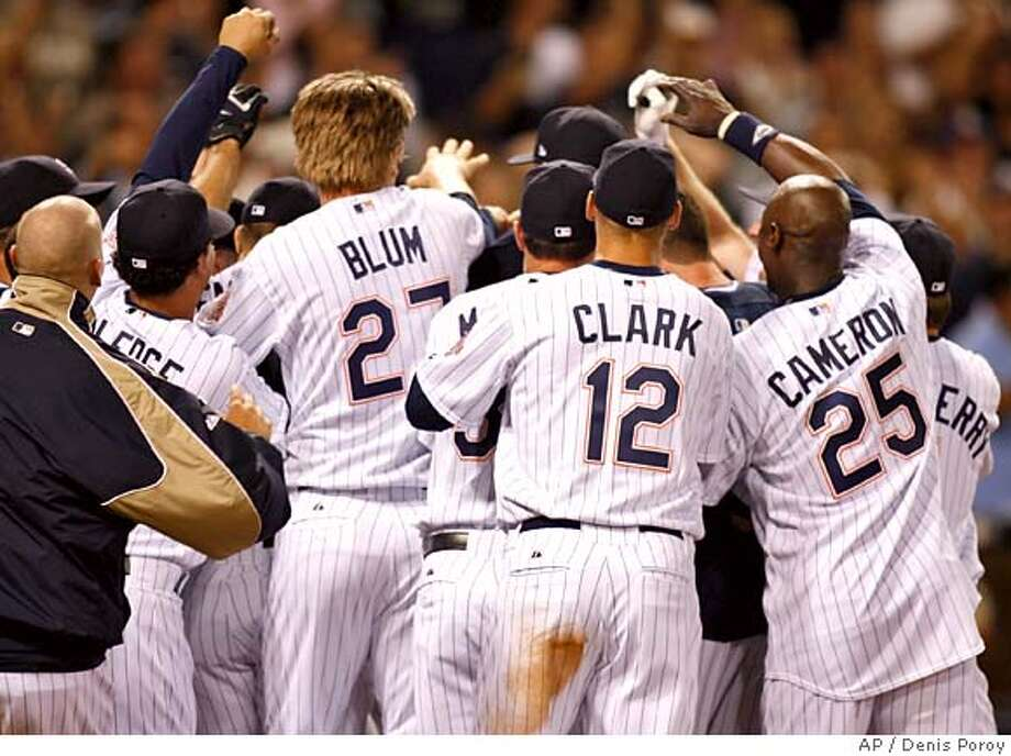 San Diego Padres players mob Khalil Greene, not visible, after Greene hit a walk off home run hit off of San Francisco Giants pitcher Dan Glese in tenth inning of a baseball game Friday, Sept. 14, 2007 in San Diego. The Padres won 5-4. (AP Photo/Denis Poroy) Photo: Denis Poroy
