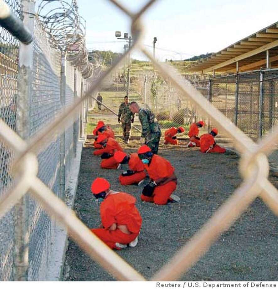 Detainees sit in a holding area watched by military police at Camp X-Ray inside Naval Base Guantanamo Bay, Cuba, during their processing into the temporary detention facility in this January 11, 2002 file photo. The United States on February 16, 2006 faced mounting international calls to close its Guantanamo prison camp with U.N. investigators saying detainees there faced treatment amounting to torture. In a 40-page report, which had been largely leaked, five United Nations special envoys said the United States was violating a host of human rights, including a ban on torture, arbitrary detention and the right to a fair trial. EDITORIAL USE ONLY REUTERS/U.S. Department of Defense/Petty Officer 1st class Shane T. McCoy/Handout/FileRan on: 02-17-2006  Ran on: 02-17-2006 0 Photo: HO