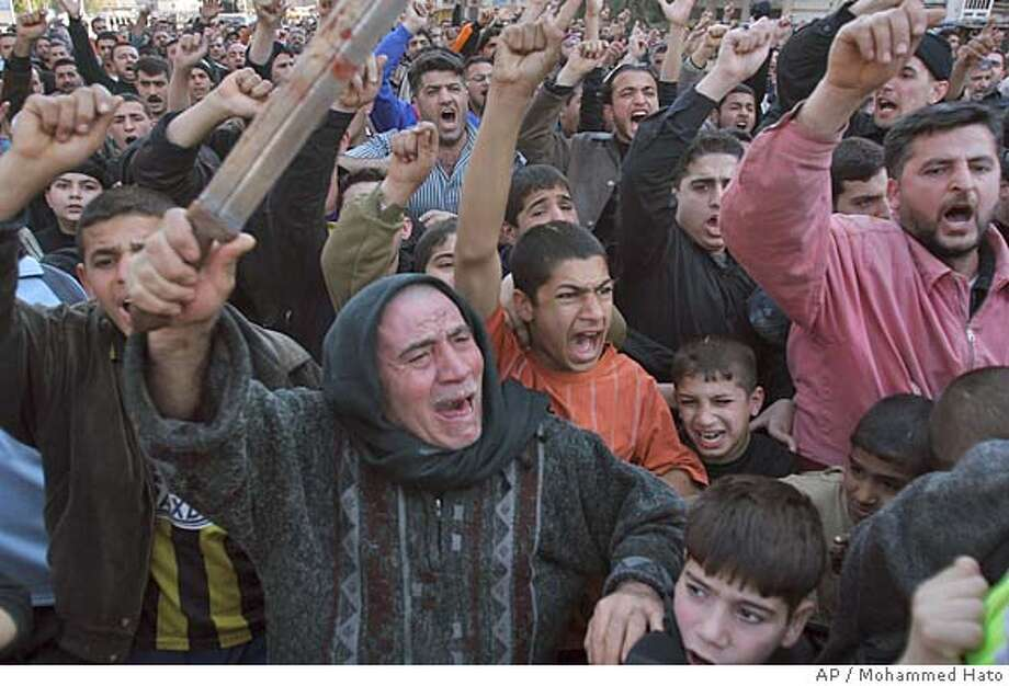 Shiite protesters rally waving a sword and fists in Baghdad, Thursday, Feb. 23, 2006. Shiite protesters attacked scores of Sunni mosques across Iraq on in retaliation for the bombing of one of Shiite Islam's holiest shrines. (AP Photo/Mohammed Hato) Photo: MOHAMMED HATO