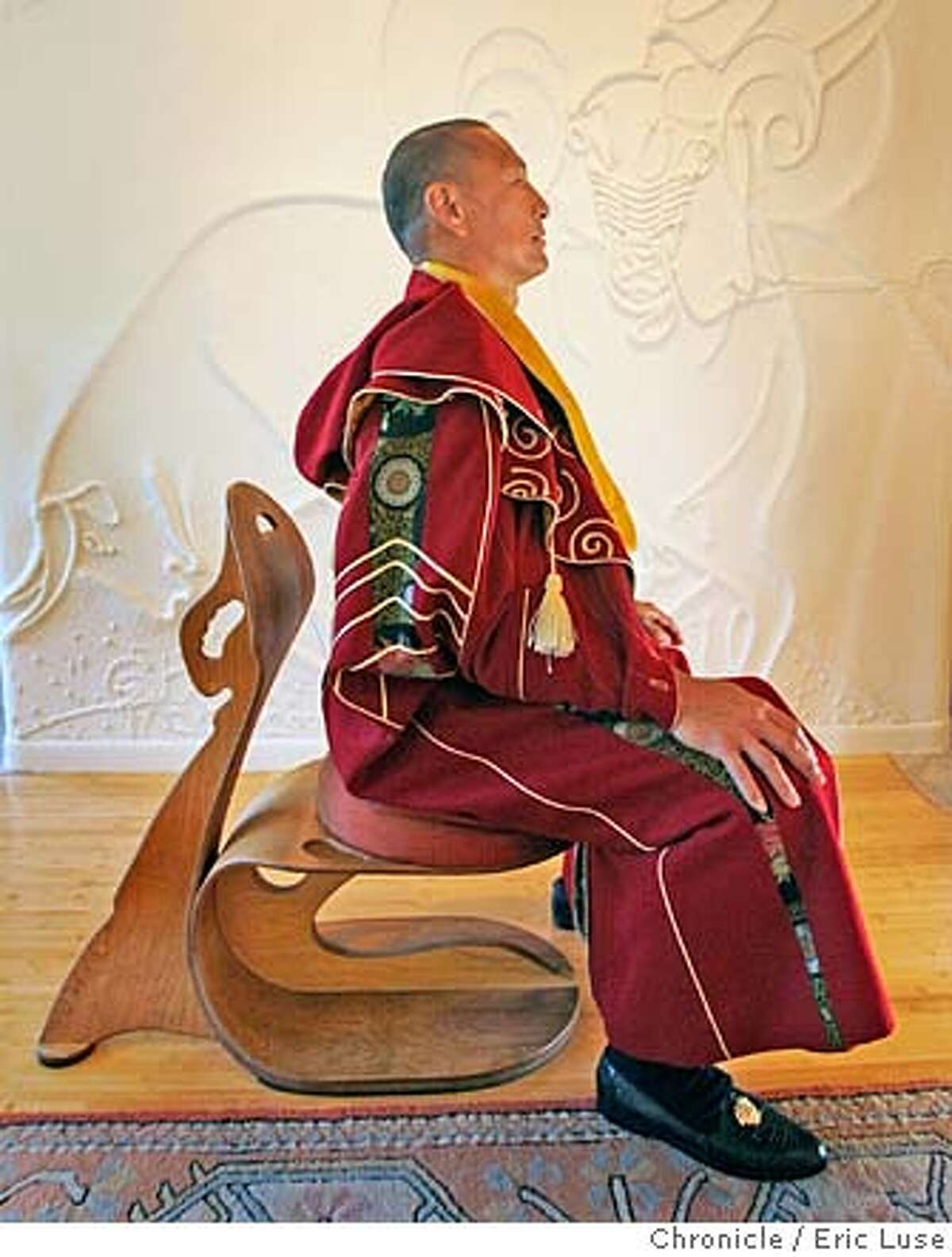 architect_tsui100.JPG Architect Eugene Tsui at home in Emeryville. He is wearing a self designed cape of moving architectural clothing that protects from elements and adapts to physical activity. He also designed the chair based on principals of the least amount of material used for maximum strength. This wall has the symbols of a Ram's head and 2 bulls symbolic of his children's signs. Photographer: Eric Luse / The Chronicle names (cq) from source Eugene Tsui MANDATORY CREDIT FOR PHOTOG AND SF CHRONICLE/NO SALES-MAGS OUT