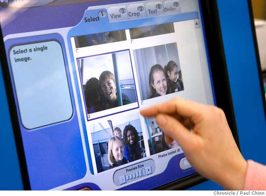 Jennifer Kuyat creates personalized greeting cards using the touch screen interface of HP's new Photosmart Studio kiosk at a Long's drug store in Walnut Creek, Calif. on 2/15/06.  PAUL CHINN/The Chronicle MANDATORY CREDIT FOR PHOTOG AND S.F. CHRONICLE/ - MAGS OUT Photo: PAUL CHINN