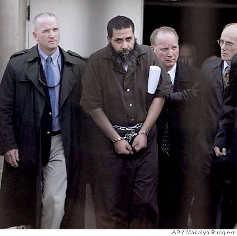 Marwan Othman El-Hindi, 42, center, a U.S. citizen born in Jordan, is escorted by officials after being indicted by a federal grand jury on terrorism charges, Tuesday, Feb. 21, 2006, at the Federal Courthouse, in Toledo, Ohio. Three Muslim men from the Middle East were charged Tuesday with plotting terrorist attacks against U.S. and coalition troops in Iraq and other countries. (AP Photo/Madalyn Ruggiero) EDS NOTE: IMAGE SHOT THROUGH BARS Photo: MADALYN RUGGIERO