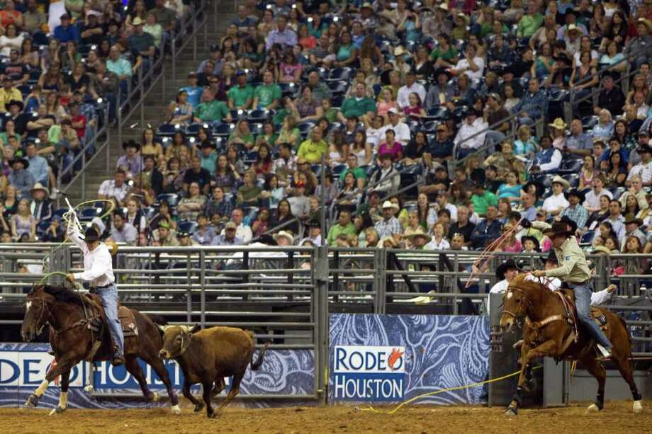 Cory Graham and Monty Petska compete in the Super Series Championship Team Roping at the Houston Livestock Show and Rodeo on Saturday, March 17, 2012, in Houston. The pair won the championship in the event. Photo: Smiley N. Pool, Houston Chronicle / © 2012  Houston Chronicle