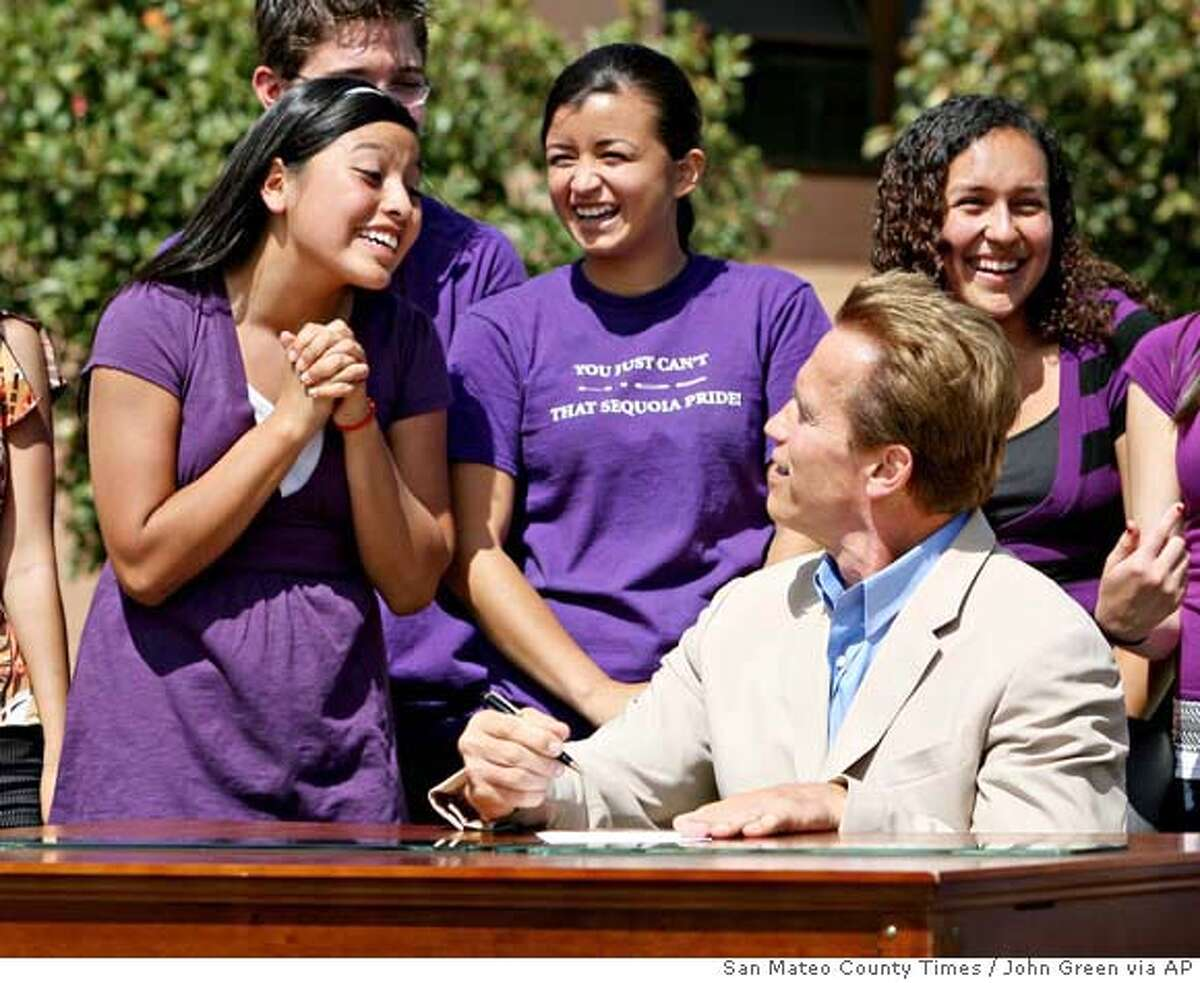 Sandra Torres, left, the junior class president at Sequoia High School in Redwood City, Calif., pleads with California Gov. Arnold Schwarzenegger for the pen he used to sign a bill on Thursday, Sept.13, 2007. The bill bans teenage drivers from using electronic devices such as cell phones, pagers and laptops while driving. (AP Photo/ San Mateo County Times, John Green) **NO SALES MAGS OUT MANDATORY CREDIT** NO SALES MAGS OUT MANDATORY CREDIT