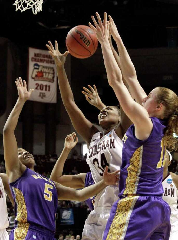 Texas A&M's Karla Gilbert (34) reaches for a rebound with Albany's Julie Forster (11) and Ebone Henry (5) during the first half of an NCAA tournament first-round college basketball game on Saturday, March 17, 2012, in College Station, Texas. (AP Photo/David J. Phillip) Photo: David J. Phillip, Associated Press / AP