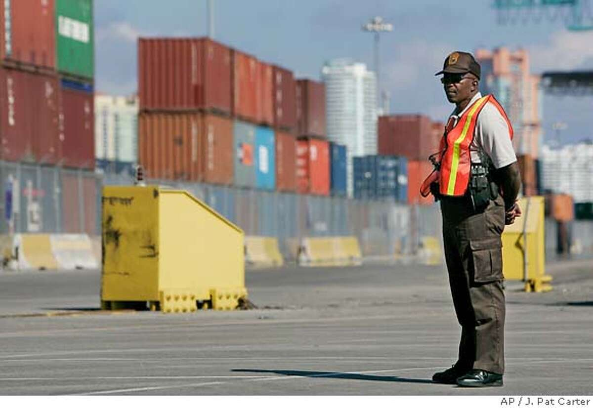 An unidentified official guards a shipping container storage area at the Port of Miami Tuesday, Feb. 21, 2006. President Bush said Tuesday that a deal allowing an Arab company to take over six major U.S. seaports, including New York's, should go forward and that he would veto any congressional effort to stop it. (AP Photo/J. Pat Carter)