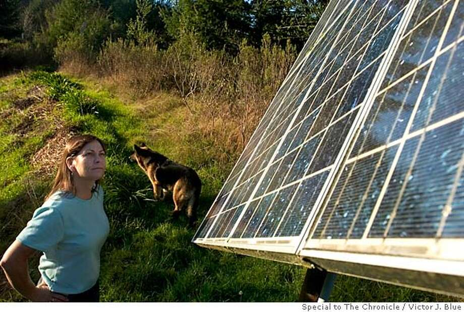 Linda Parkinson looks at solar panels that need cleaning at her off-the-power-grid home in Arcata (Humboldt County). Photo by Victor J. Blue, special to The Chronicle