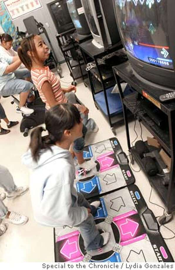 Cecil Avenue Middle School students Christina Alvarez, 12, and Ashley Robinson, 12, laugh as they try to dance to the steps of Dance Dance Revolution in Delano. Photo by Lydia Gonzales, special to the Chronicle