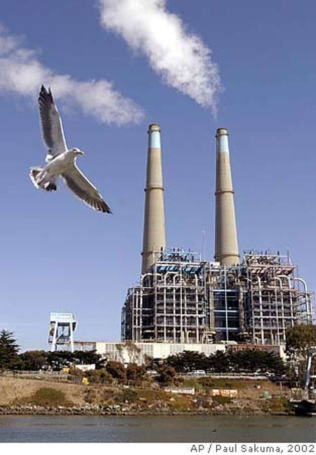 A seagull flies in front of a power plant in Watsonville, Calif., Tuesday, Sept. 17, 2002. The nation's industrial sector, hardest hit by last year's recession, stumbled in August, with production falling for the first time in eight months. Much of the weakness came from a sharp 2.5 percent drop in output at gas and electric utilities. (AP Photo/Paul Sakuma) Photo: PAUL SAKUMA