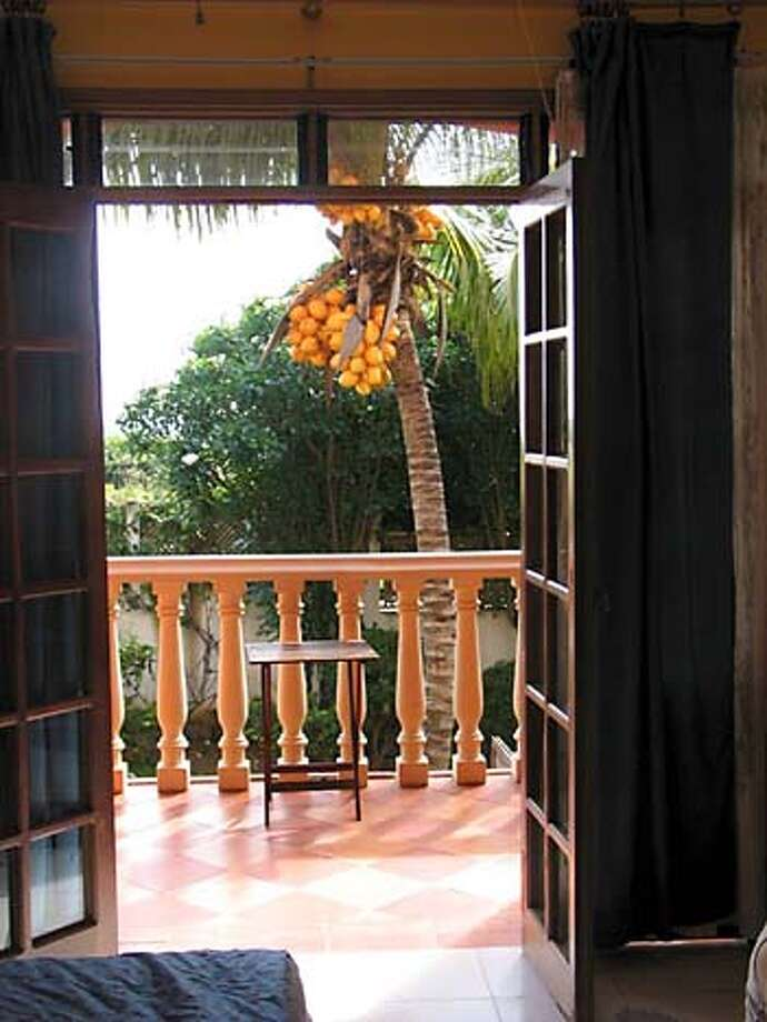 Doorway to Caribbean: A room at Hotel Casa Rita on Venezuela's Isla de Margarita opens onto a balcony that overlooks the garden, where palm trees are heavy with coconuts and harmless snakes and iguanas roam. The ocean, a few blocks away, is also visible. Chronicle photo, 2005, by Christine Delsol