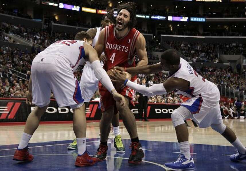Rockets forward Luis Scola, center, is defended by Los Angeles Clippers' Blake Griffin, left, and Ch