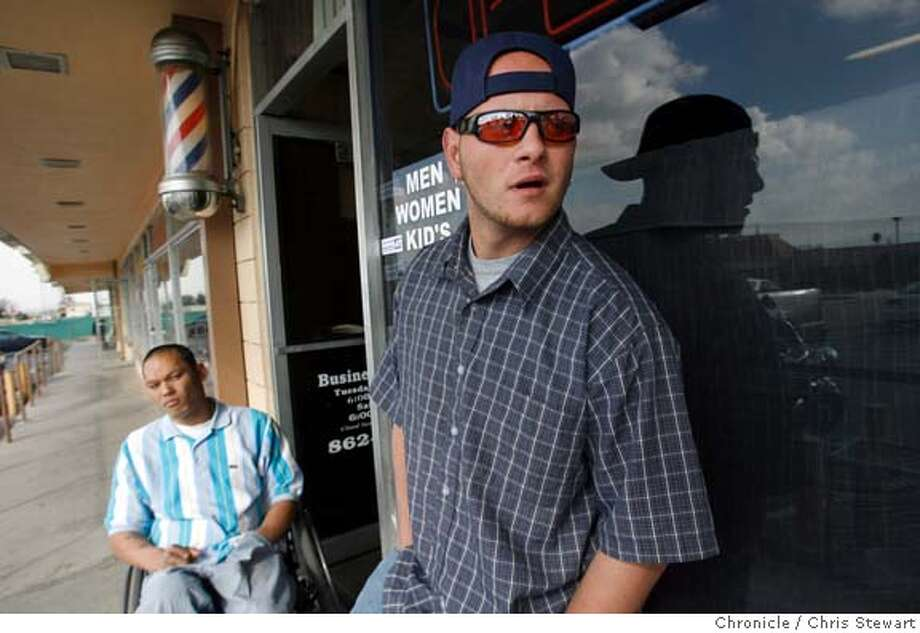 """highland_081_cs.JPG  Event on 2/17/06 in Highland. Barber Daniel McGee, 22, stands outside his family barber shop with David Lam, 33, (in wheelchair), who works at a nearby business in the city of Highland, California. The city council of Highland, in San Bernardino County, unanimously passed a resolution which states, in part, """"the City of Highland will not spend public money going to the City of San Francisco. We will not spend one dime of public money."""" """"We realize that in the rest of the country, California is known as the land of kooks and nuts because of what happens in San Francisco,"""" said Highland City Council member Larry McCallon. """"We wanted to let the rest of the country know that California, and specifically Highland, supports our military, that San Francisco does not speak for California."""" McGee offers a different opinion. """"I don't think we should be over there (in Iraq). Our people are dying there everyday.""""  Chris Stewart / The Chronicle MANDATORY CREDIT FOR PHOTOG AND SF CHRONICLE/ -MAGS OUT Photo: Chris Stewart"""