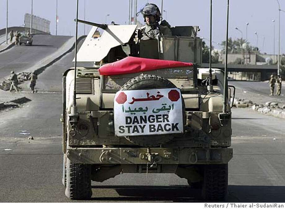 A U.S. soldier secures the scene of a roadside bomb attack aboard an armoured vehicle in Baghdad February 18, 2006. A U.S. soldier was killed on Saturday when his vehicle was struck by a roadside bomb in eastern Baghdad, the U.S. military said. REUTERS/Thaier al-SudaniRan on: 02-19-2006  A U.S. soldier aboard an armored vehicle secures the scene of a roadside bomb attack in Baghdad. Photo: THAIER AL-SUDANI