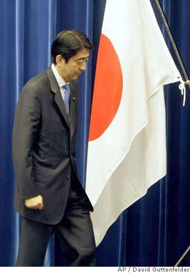 """Japanese Prime Minister Shinzo Abe leaves the podium after announcing his resignation at a nationally televised press conference in Tokyo Wednesday, Sept. 12, 2007. """"In the present situation, it is difficult to push ahead with effective policies that win the support and trust of the public,"""" he said. (AP Photo/David Guttenfelder) Photo: David Guttenfelder"""