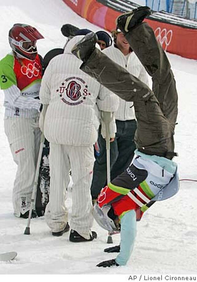Tanja Frieden of Switzerland makes a handstand after winning a gold medal, as American Lindsey Jacobellis, rear left, finished second after crashing in sight of the finish line in the final of the Women's Snowboard Cross competition at the Turin 2006 Winter Olympic Games in Bardonecchia, Italy, Friday, Feb. 17, 2006. Jacobellis took a silver medal, Dominique Maltais of Canada bronze. (AP Photo/Lionel Cironneau) Photo: LIONEL CIRONNEAU