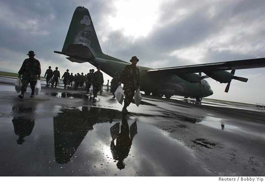 Philippines soldiers unload aids from a military plane for mudslide victims at Tacloban airport in central Philippines February 18, 2006. Hundreds of people were feared dead in the remote farming village of Guinsaugon, near Saint Bernard town in southern Leyte province, after mudslides triggered by heavy rains buried houses and an elementary school packed with children on Friday, officials and witnesses said. REUTERS/Bobby YipRan on: 02-18-2006  Philippine soldiers unload aid for mudslide victims from a military plane at Tacloban airport.Ran on: 02-18-2006  Philippine soldiers unload aid for mudslide victims from a military plane at Tacloban airport. Photo: BOBBY YIP