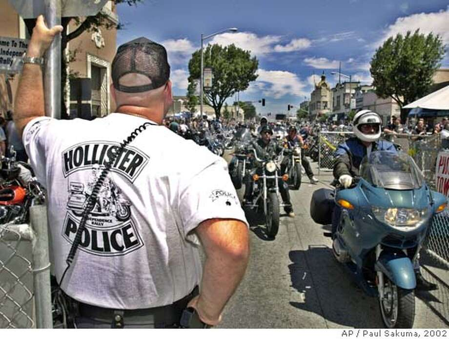 Hollister police officer Dave Mustard stands guard as motorcyclists cruise on the main street in downtown Hollister, Calif., during the Hollister Independence Rally, Saturday, July 6, 2002. (AP Photo/Paul Sakuma) Photo: PAUL SAKUMA