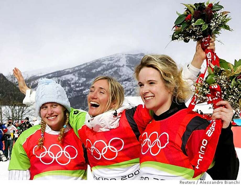Switzerland's Tanja Frieden (C), Lindsey Jacobellis of the U.S. (L) and Canada's Dominique Maltais celebrate on the winners podium of the women's snowboard cross competition at the Torino 2006 Winter Olympic Games in Bardonecchia, Italy, February 17, 2006. REUTERS/Alessandro Bianchi Photo: ALESSANDRO BIANCHI