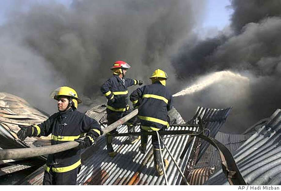 Firefighters extinguish a fire in the Karrada neighborhood of central Baghdad, Iraq, Tuesday, Sept. 11, 2007. Police said the blaze affected a large store that sells electronic appliances. (AP Photo/Hadi Mizban) Photo: HADI MIZBAN