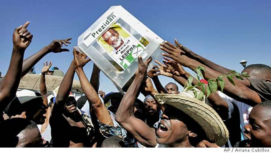 Supporters of elected President Rene Preval lift a ballot box with his campaign poster attached while celebrating at the National Palace in Port-au-Prince, Haiti, Thursday, Feb. 16, 2006. Haitians began celebrating in the street Thursday as word quickly spread that Rene Preval, a former president who is hugely popular among the poor, was declared the winner of the presidential election overnight. (AP Photo/Ariana Cubillos) **EFE OUT** Photo: ARIANA CUBILLOS