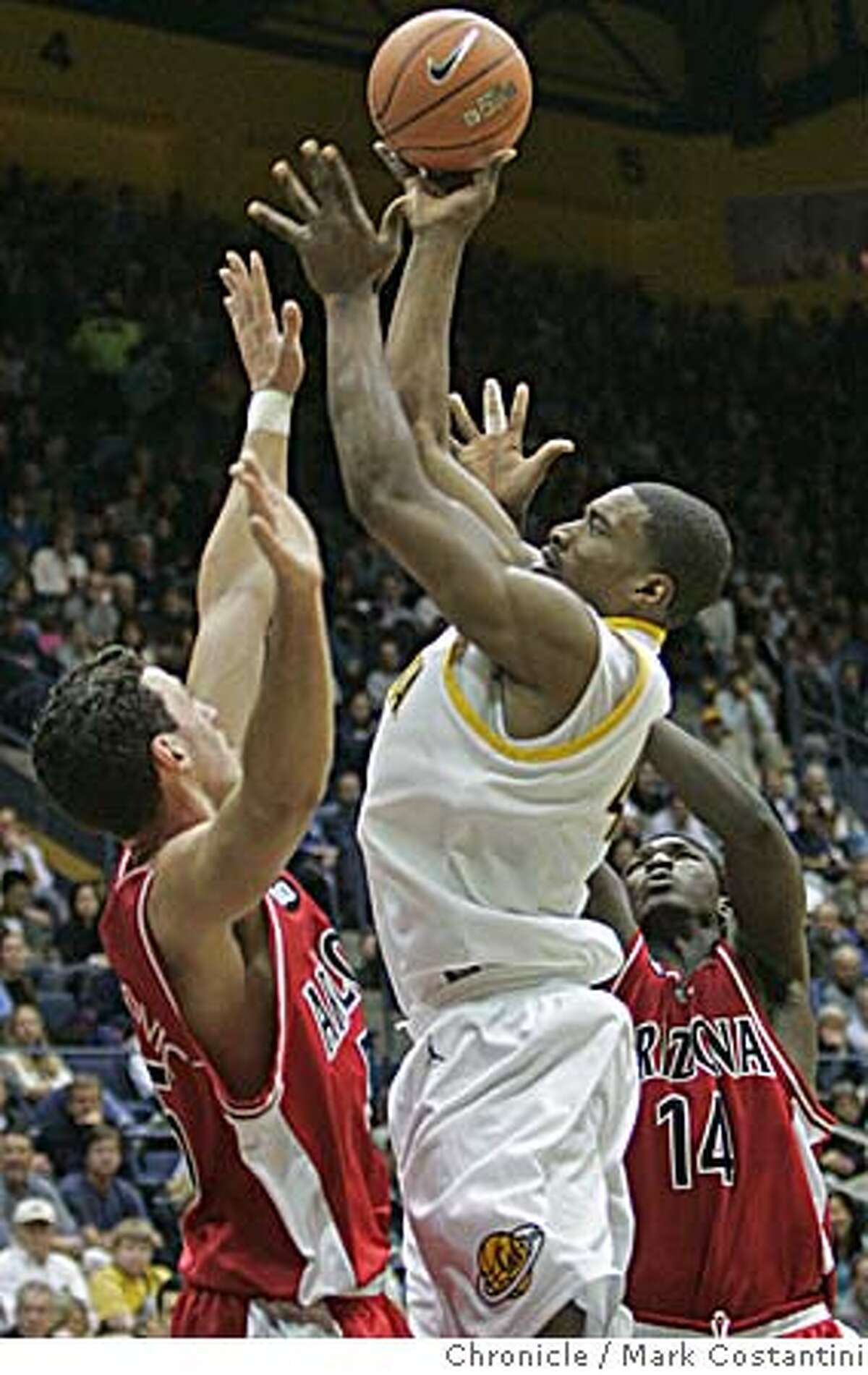 CAL_0226 {2/16/06} Cal's Leon Powe shoots and scores as Arizona defenders (l) Ivan Radenovic and Mohamed Tangara(14) cover on the play. Cal vs. Arizona in men's basketball. EVENT ON 2/16/06 IN BERKELEY. PHOTO: MARK COSTANTINI/SAN FRANCISCO CHRONICLE