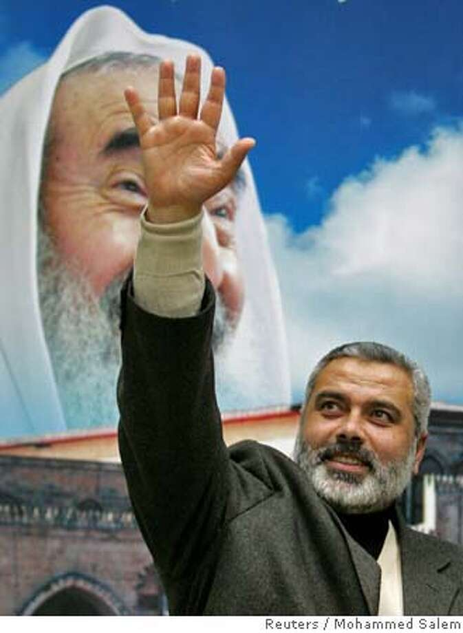 Hamas leader Ismail Haniyeh waves in front a poster of late Hamas leader Sheikh Ahmed Yassin in Gaza February 16, 2006. Hamas leader, Ismail Haniyeh, denied the militant Islamic group had nominated him as Palestinian prime minister. REUTERS/Mohammed SalemRan on: 02-17-2006  Ismail Haniya, in front of a poster of slain Hamas leader Sheikh Ahmed Yassin, reportedly is the group's choice for prime minister. Photo: MOHAMMED SALEM