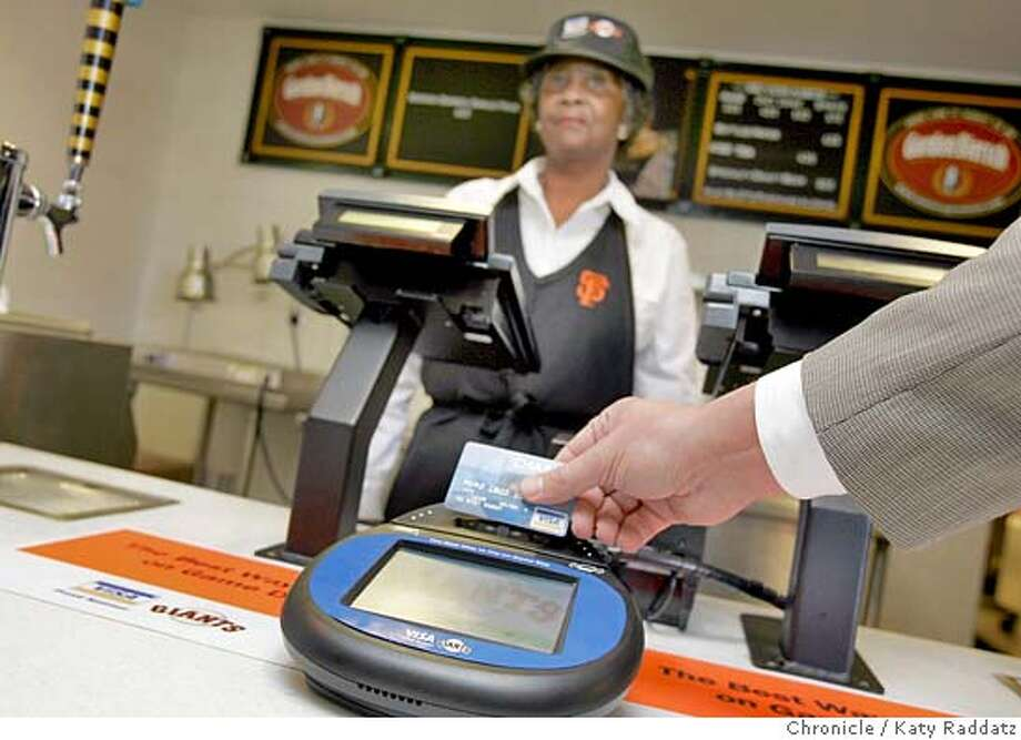 """CONTACTLESS17_003_RAD.JPG SHOWN: Cashier Lucille Lawrence of San Francisco rings up a cashless transaction for an order of garlic fries on the Club level of AT&T Park in a demonstration. Brian Tripett (of the Visa Corp.) holds a credit card over a special card reader. Story is about credit card companies wanting the consumer to say goodbye to cash. Visa, MasterCard and American Express are pushing """"contactless cards"""" to use to buy something quick and cheap--instead of swiping card and signing, one waves the card over a reader. Photo taken on 2/15/06, in San Francisco, CA.  By Katy Raddatz / The San Francisco Chronicle MANDATORY CREDIT FOR PHOTOG AND SF CHRONICLE/ -MAGS OUT Photo: Katy Raddatz"""