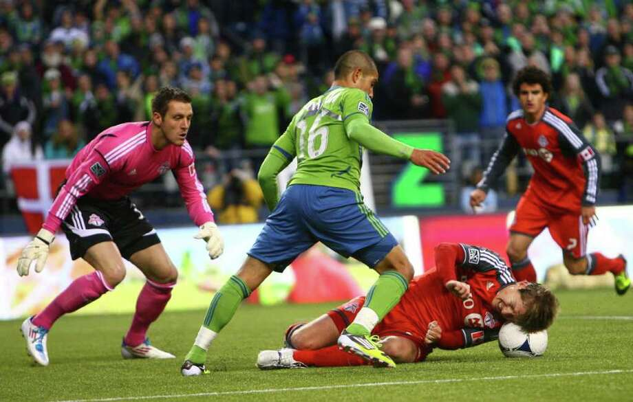 Toronto FC player Torsten Frings tries to stop the ball with his head as Seattle Sounders player David Estrada prepares to score a goal in the first half of the Seattle Sounders MLS season opener against Toronto FC on Saturday, March 17, 2012 at CenturyLink Field in Seattle. Photo: JOSHUA TRUJILLO / SEATTLEPI.COM