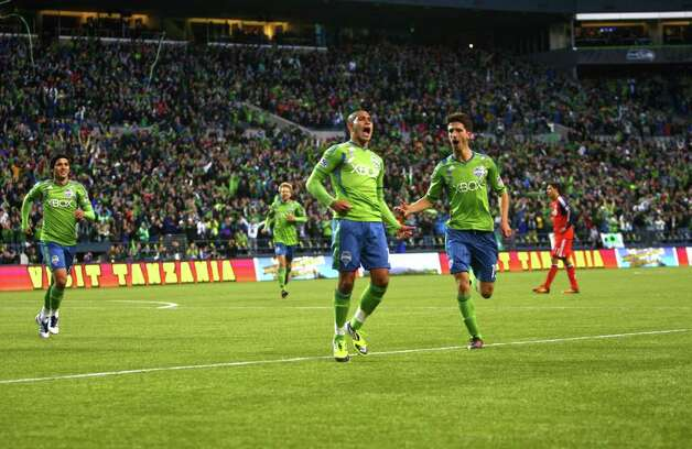 David Estrada, center, celebrates the first of his three goals with teammates Alvaro Fernandez (15) and Fredy Montero (17), left. Photo: JOSHUA TRUJILLO / SEATTLEPI.COM