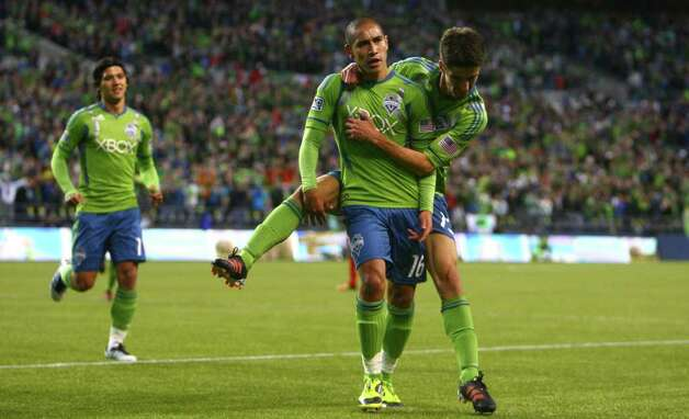 David Estrada, center, celebrates with teammate Alvaro Fernandez (15) after Estrada scored a first-half goal. Photo: JOSHUA TRUJILLO / SEATTLEPI.COM