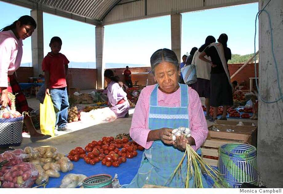 """Brigida Cruz, selling produce in Oaxaca, Mexico, tunes in to Radio Biling�e: """"Maybe if somebody else's relatives are doing OK, so are yours."""" Photo by Monica Campbell, special to The Chronicle"""
