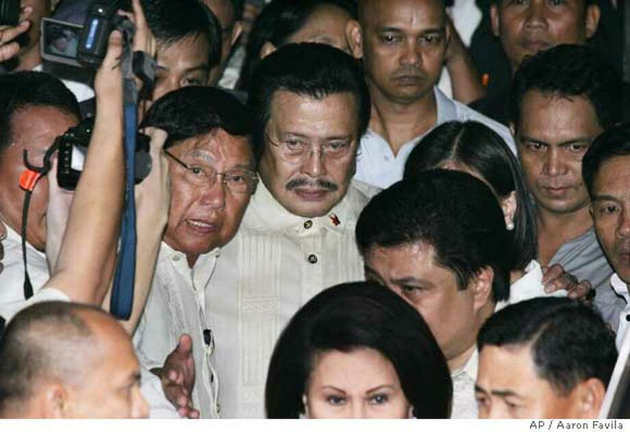 Deposed Philippine President Joseph Estrada, center, is escorted out the Sandiganbayan anti-graft court in suburban Quezon City, north of Manila, on Wednesday Sept. 12, 2007. Estrada, who once pulled off the Philippines' biggest election victory, was sentenced to life in prison Wednesday after a landmark six-year trial on charges that he took bribes and kickbacks in office. (AP Photo/Aaron Favila) Photo: Aaron Favila