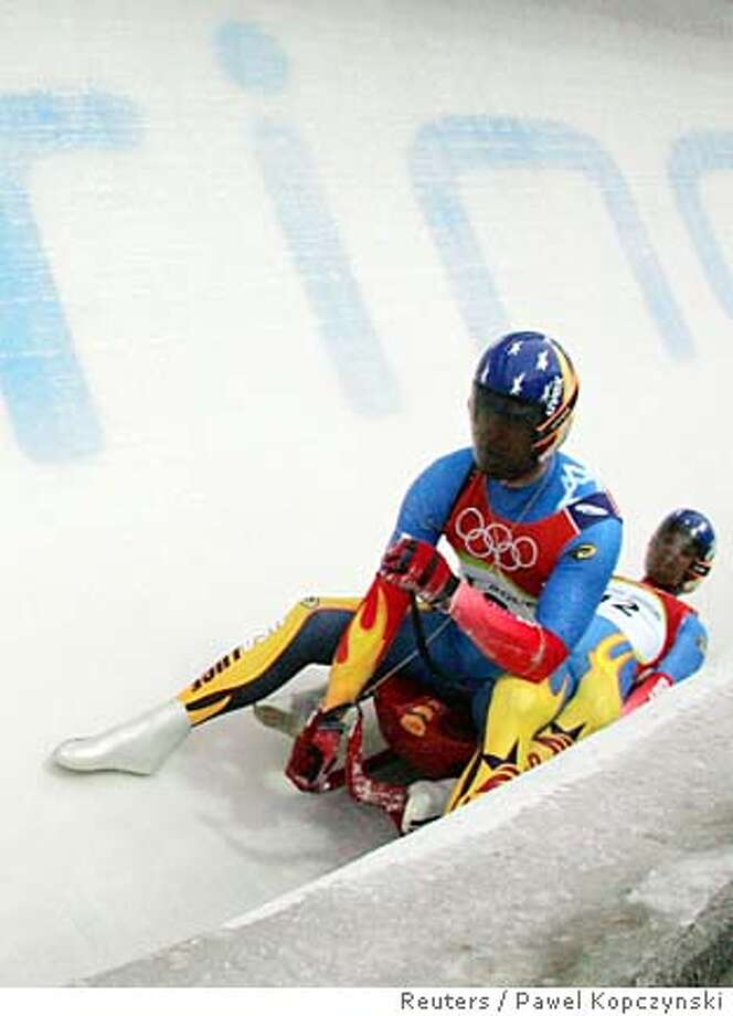 Mark Grimmette (left) and Brian Martin of the U.S. react after crashing during the doubles luge event at the Torino 2006 Winter Olympic Games in Cesana Pariol, Italy February 15, 2006. REUTERS/Pawel Kopczynski Photo: PAWEL KOPCZYNSKI
