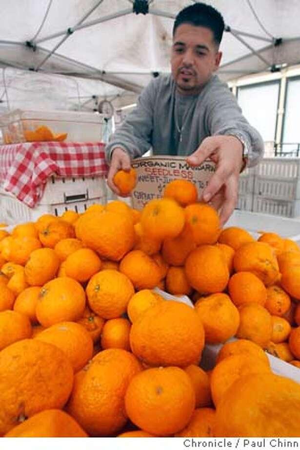 Joseph Serna, from Twin Girls Farms, restocks the organic seedless mandarins at the Old Oakland Farmers' Market in Oakland, Calif. on 2/3/06.  PAUL CHINN/The Chronicle Photo: PAUL CHINN