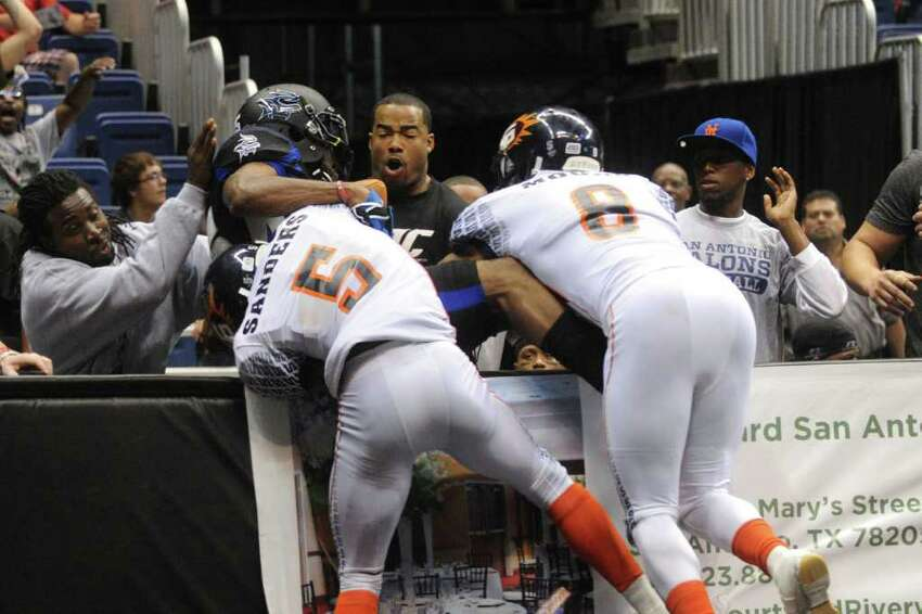Jomo Wilson (15) of the San Antonio Talons holds on to a touchdown pass as he falls over the barrier as he is tackled by Terrance Sanders (5) and Terance Moore (8) of the Spokane Shock during second-half AFL action in the Alamodome on Saturday, March 17, 2012. San Antonio lost the game, 63-60. Billy Calzada / San Antonio Express-News