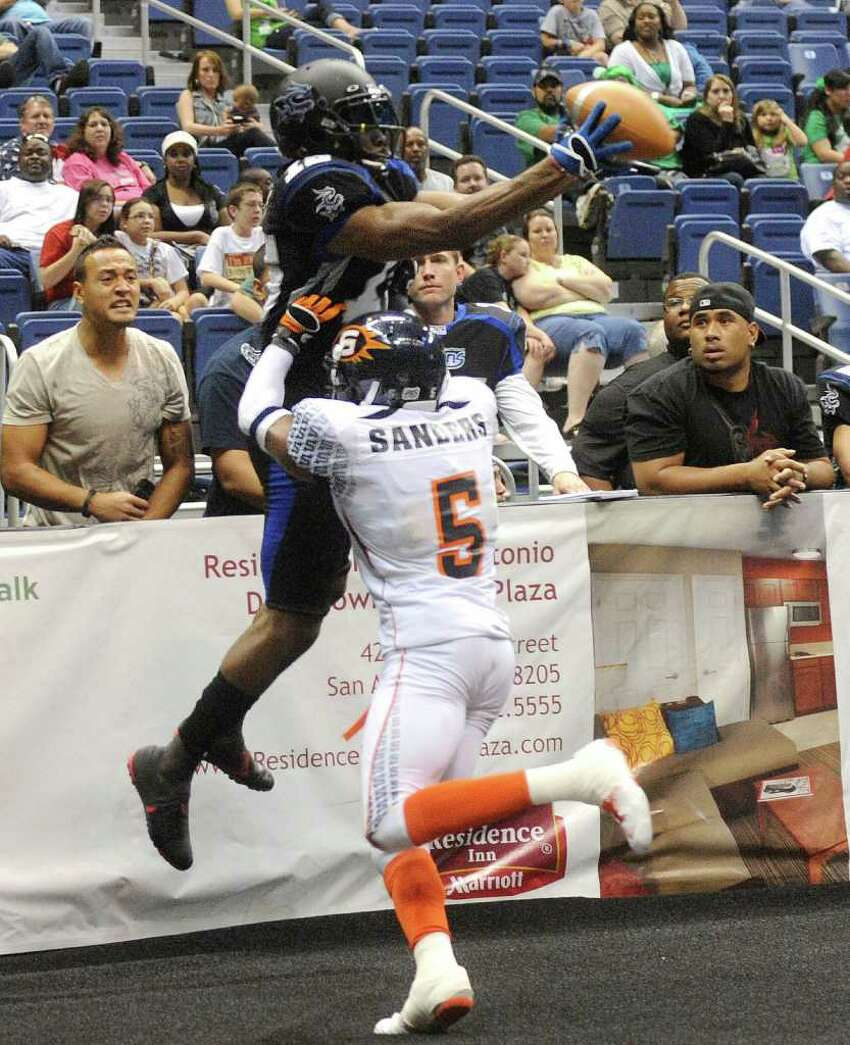 Jomo Wilson (15) of the San Antonio Talons hauls in a touchdown pass before he is tossed over the barrier during second-half AFL action against the Spokane Shock in the Alamodome on Saturday, March 17, 2012. San Antonio lost the game, 63-60. Billy Calzada / San Antonio Express-News