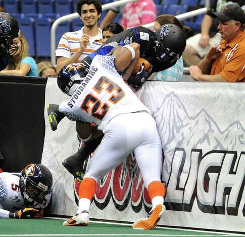 Shaun Kauleinamoku (5) of the San Antonio Talons is pinned against the wall by Patrick Stoudamire of the Spokane Shock during AFL action in the Alamodome on Saturday, March 17, 2012.  Billy Calzada / San Antonio Express-News Photo: Billy Calzada, Express-News / San Antonio Express-News